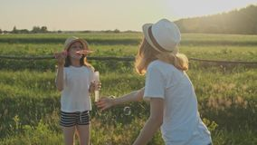 Children blowing soap bubbles, two girls playing in nature stock video footage
