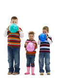 Children blowing up toy balloons Stock Images