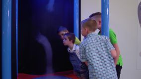 Children blows at artificial tornado in museum of popular science. And technology. Group of teenagers explores the principle of creating the natural whirlpool stock footage