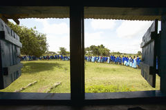Children in blue lineup at school through interior of window in schoolroom near Tsavo National Park, Kenya, Africa Royalty Free Stock Images
