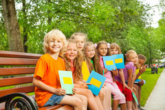 Children with blue notebooks sit in row on bench Royalty Free Stock Photos