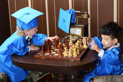Children in blue suits play chess Royalty Free Stock Photos