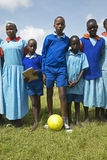 Children in blue uniforms holding soccer ball at school near Tsavo National Park, Kenya, Africa Royalty Free Stock Images