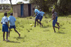 Children in blue uniforms playing soccer at school near Tsavo National Park, Kenya, Africa stock image