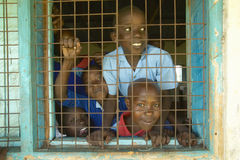 Children in blue uniforms in window at school near Tsavo National Park, Kenya, Africa Royalty Free Stock Photo