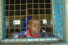 Children in blue uniforms in window at school near Tsavo National Park, Kenya, Africa Royalty Free Stock Photography