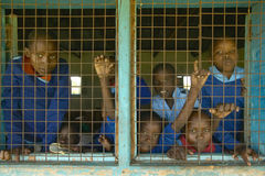 Children in blue uniforms in window at school near Tsavo National Park, Kenya, Africa Stock Image