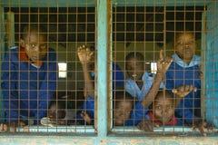 Children in blue uniforms in window at school near Tsavo National Park, Kenya, Africa Stock Image
