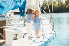 The children on board of sea yacht. Drinking orange juice. The teen or child girls against blue sky outdoor. Colorful clothes. Kids fashion, sunny summer, river royalty free stock photo
