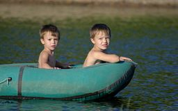 Children in a boat. Two boys, aged 3 and 6, in green rowing boat Stock Photography