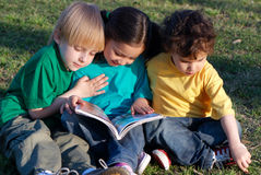 Children with the book on a grass in park Royalty Free Stock Photos