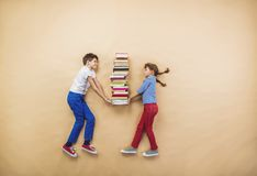Children with books. Happy children playing with group of books in studio Stock Images