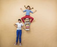 Children with books. Happy children playing with group of books in studio Stock Photography