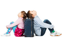 Children bored of travelling. Young boy and girl sitting back to back against a suitcase, their eyes shut with  tiredness and boredom from travelling Stock Photo