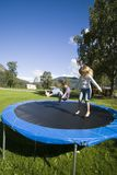 Children bouncing. Boy and girl having fun, bouncing on a trampoline. Camp site surroundings, Norway Stock Photos