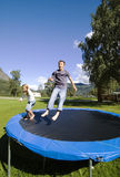 Children bouncing. Boy and girl having fun, bouncing on a trampoline. Camp site surroundings, Norway Stock Images