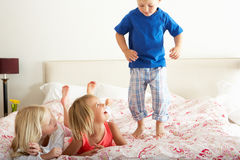 Children Bouncing On Bed. Smiling Stock Photo
