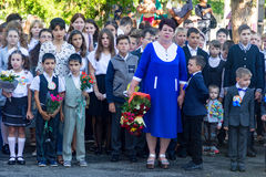 Children with bouquets of flowers enrolled in the first class at school with teachers and high school students at the solemn openi Stock Photography