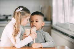 Children, Boy And Girl Eating Ice Cream Cone In The Kitchen Are Very Fun To Share With Each Other Stock Image