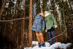 Children Boy And Girl Walking In Snow Forest In A Winter Day. Teenagers Having Trip And Rest In Weekend Outdoor Stock Image