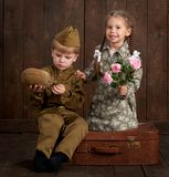 Children boy are dressed as soldier in retro military uniforms and girl in pink dress sitting on old suitcase, dark wood backgroun stock image