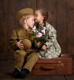 Children boy are dressed as soldier in retro military uniforms and girl in pink dress sitting on old suitcase, dark wood backgroun royalty free stock photography