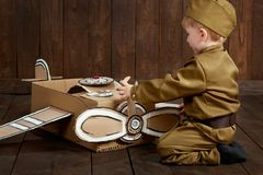 Children boy are dressed as soldier in retro military uniforms repair an airplane made of cardboard box, dark wood background, ret stock photos