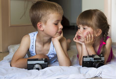 Children boy and girl brother and sister playing with cameras lo Stock Photography