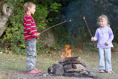 Children boy and girl playing with fire on natural backgroun Royalty Free Stock Photos