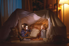 Children boy and girl playing and frighten each other in  tent Stock Photos