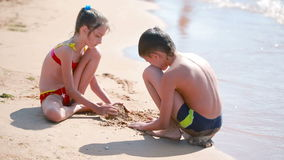 Children. boy and girl playing with sand on the beach. build a sand castle stock video footage