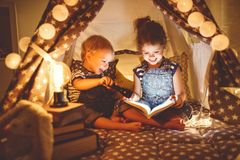 Children boy and girl reading book with flashlight in tent. At night stock image