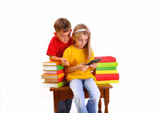 Children - a boy and girl reading e-book. Surrounded by several books isolate on white background Stock Images