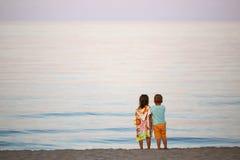 Children boy and girl romance on the seashore colorful sunset. Children boy and girl romance on the seashore colorful sunset Stock Image