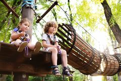 Children - a boy and a girl in the rope park pass obstacles stock image