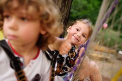 Children - a boy and a girl in the rope park pass obstacles stock photography