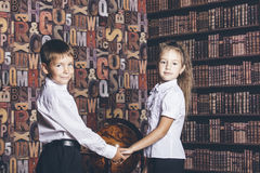 Children boy and girl of school age consider a globe Stock Photo