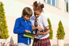 The children show each other something on the tablets in the sch. Children - a boy and a girl stand with tablets in the school yard and smile. The children show royalty free stock photography
