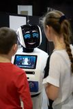 Children boy and girl talking, playing with an android robot. stock photos
