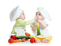 Children boy girl eating healthy  food. Children boy and girl wearing a chef hat with healthy  food vegetables Royalty Free Stock Image
