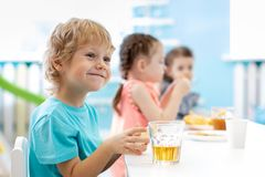 Children boy and girls at daycare lunch table royalty free stock photo