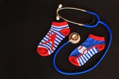 Children boy socks  and stethoscope, symbolizing children healthcare / pediatric care Stock Photos