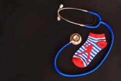 Children boy socks  and stethoscope, symbolizing children healthcare / pediatric care Royalty Free Stock Photos