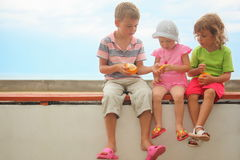 Children: boy and two girls sitting on a brach Stock Photography