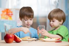 Children boys eating healthy food at home Royalty Free Stock Photo