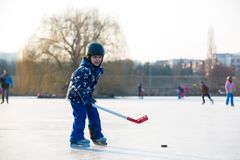 Children, playing hockey and skating in the park on frozen lake, wintertime on sunset royalty free stock images