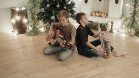 Children, boys with musical instruments, guitar and saxophone playing music on fireplace background and Christmas decor. Dolly shot two kids, boys with musical stock video footage