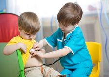 Children boys play doctor at home Stock Images