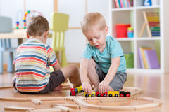 Children boys playing rail road toy in nursery Stock Photography