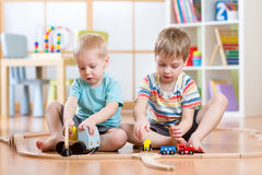Children boys playing rail road toy in nursery Stock Image